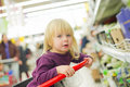 Little girl on cart in supermarket Stock Image
