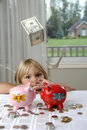 Little girl, cash and piggy banks Royalty Free Stock Photography
