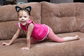 Little girl with cat face painting on couch Royalty Free Stock Photo