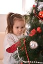 Little girl celebrating christmas decorating tree at home Stock Images