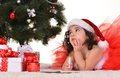 Little girl celebrating christmas lying near tree at home Stock Image