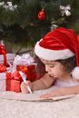 Little girl celebrating christmas lying near tree at home Stock Photo