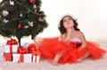Little girl celebrating christmas lying near tree at home Royalty Free Stock Image