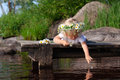 Little girl in chamomile wreath is dropping petals into the water lying on a wooden bridge and petal Stock Photography