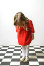 Little girl on checkered floor like alice in wonderland Stock Image