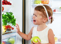 Little girl child is crying and acting about fridge with fruit Royalty Free Stock Photo