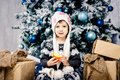 Little girl child of five years sitting on the floor near Christmas tree decorated with toys, balls. In the hands holds an orange Royalty Free Stock Photo