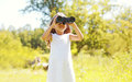 Little girl child looks in binoculars outdoors in summer