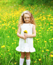 Little girl child outdoors on the grass with yellow dandelion Royalty Free Stock Photo