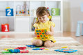 Little girl child playing with lots of colorful plastic digits or numbers indoors.