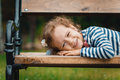 Little girl child portrait of lying on bench in a park leisure in the nature close up Stock Photo