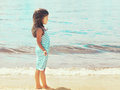 Little girl child walks on the beach near sea Royalty Free Stock Photo