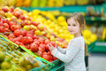 Little girl choosing pomegranate in a food store Royalty Free Stock Photo