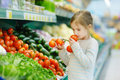 Little girl choosing tomatoes in a food store Royalty Free Stock Photo
