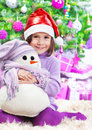 Little girl on christmas celebration cute sitting the floor under big decorated tree wearing red santa hat holding in hands white Stock Photo