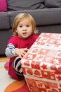 Little girl with a christmas gift cute at home Stock Photos