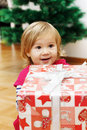 Little girl with a christmas gift cute at home Stock Image