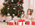 Little girl with christmas gifts sitting by tree Royalty Free Stock Image