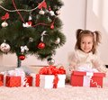 Little girl with christmas gifts sitting by tree Stock Image