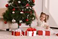 Little girl with christmas gifts sitting by tree Stock Photos