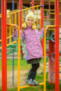 Little girl on city playground beautiful in pink jacket and yellow cap Royalty Free Stock Photos