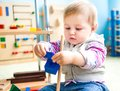 Little girl in the classroom early development cute plays with numerous toys Stock Photos