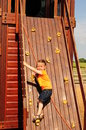 Little girl on climbing wall at outdoor playground Stock Images