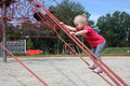 Little girl climbing through the web of ropes Royalty Free Stock Photo