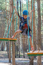 Little girl climbs on rope harness beautiful in summer city park Royalty Free Stock Photo
