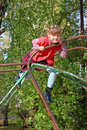 Little girl climbs and smiles on playground Royalty Free Stock Photo