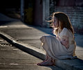 Little girl cold and alone on curb sitting in dirty dress looking Stock Images