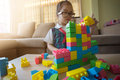 Little girl in a colorful shirt playing with construction toy blocks building a tower Royalty Free Stock Photo