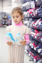 Little girl considers gym shoes and stands near shelves Royalty Free Stock Photos