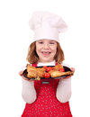 Little girl cook hold dish with chicken drumstick Stock Image