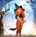 Halloween.Little girl in costume witch flying on a broom across the sky.
