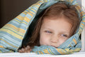 Little girl covered by blanket portrait of a cute Stock Photos
