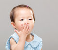 Little girl covered her mouth with gray background Royalty Free Stock Image