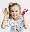Little girl covered in paint making funny faces. Royalty Free Stock Photo