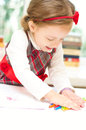 Little girl with crayon cute is drawing on white paper using Royalty Free Stock Image