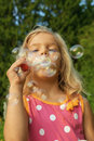 Little girl creates bubbles beautiful cheerful in summer green park Stock Photography