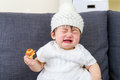 Little girl crying with bread holding on hand at home Royalty Free Stock Image