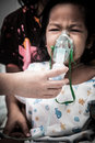 Little girl crying while getting in inhaler mask in hospital dark tone Royalty Free Stock Photo