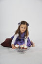Little girl with cupcakes a cute is sitting in a studio delicious in front of her Stock Photography