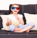 Little girl d glasses eating popcorn watching tv Royalty Free Stock Images
