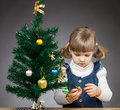 Little girl decorates the christmas tree beautiful black background Stock Images
