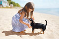 Little girl and dog on the beach in sunny summer day Royalty Free Stock Photo
