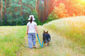 Little girl with dog walking on the dirt road back to camera Stock Photography