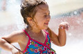 Little girl doing a happy dance laughs as she does in city fountain Stock Image