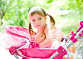 Little girl with doll and carriage Royalty Free Stock Photography