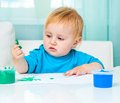Little girl draw finger paints cute baby at home in bright living room Stock Photo